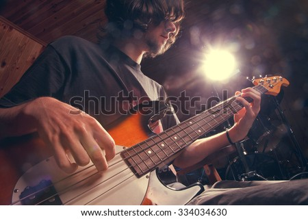 Rock star with a bass guitar - stock photo