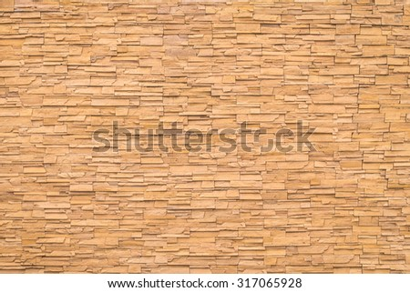 Rock stone brick tile wall aged texture detailed pattern background in dark cream beige brown color tone: Grunge ancient rustic limestone patterned backdrop for decoration in creme brown toned colour - stock photo