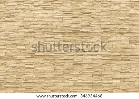 Rock stone brick tile wall aged texture detailed pattern background in dark yellow cream  brown color tone: Grunge ancient rustic limestone patterned backdrop for decoration in  beige toned colour - stock photo