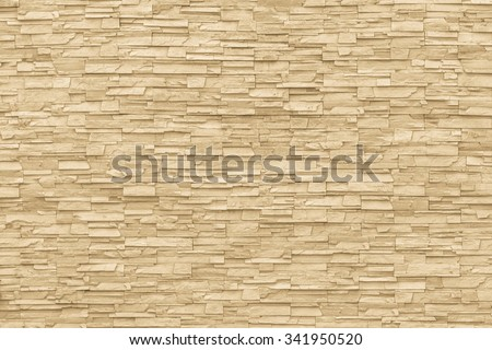 Rock stone brick tile wall aged texture detailed pattern background in light yellow cream  brown color tone: Grunge ancient rustic limestone patterned backdrop for decoration in beige toned colour - stock photo