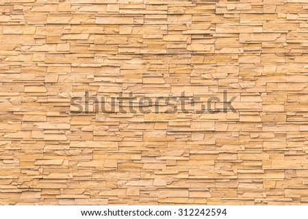 Rock stone brick tile wall aged texture detailed pattern background in yellow brown color tone: Grunge ancient rustic limestone rock patterned backdrop for decoration in orange brown toned colour   - stock photo
