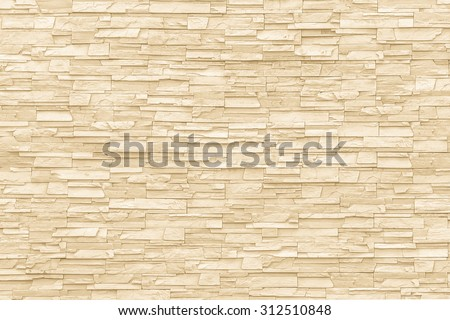 Rock stone brick tile wall aged texture detailed pattern background in yellow cream beige color tone: Grunge ancient rustic limestone patterned backdrop for decoration in creme brown toned colour    - stock photo