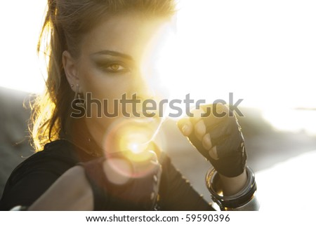 Rock style girl in an aggressive posture in the rays of bright sunshine