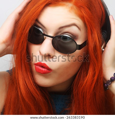 Rock style woman with headphones listening to music