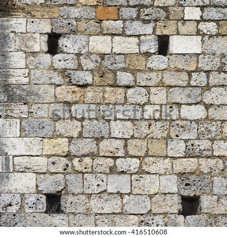 Rock wall with four holes - stock photo