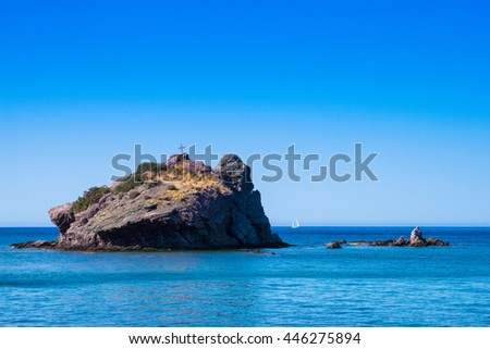 Rock with cross in the blue sea with small sail boat