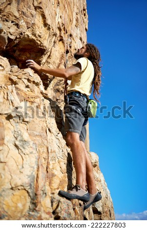 Rockclimber with dreadlocks climbing a mountain