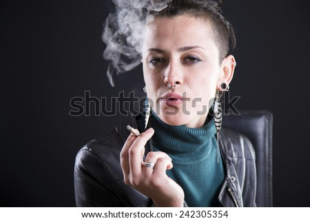 rocker girl smoking cigarette with black background - stock photo