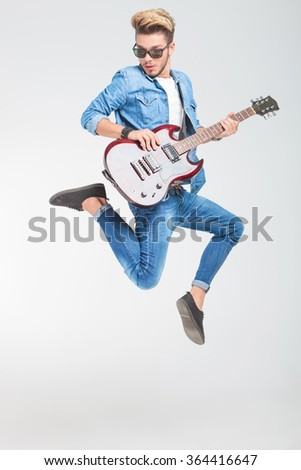 rocker jumping one side in studio while playing guitar and looking down