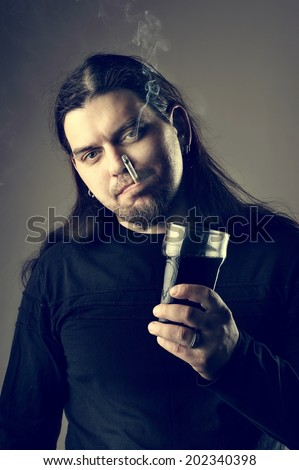 Rocker man staying with beer glass and smoking his cigarette