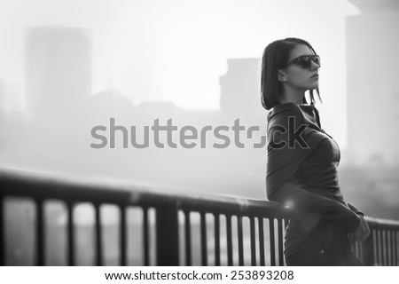 Rocker or punk woman.Young rock woman model in black leather jacket casual standing with city background.Rock bad girl.Sexy attractive woman with punk rock fashion styling.Image toned and noise added - stock photo