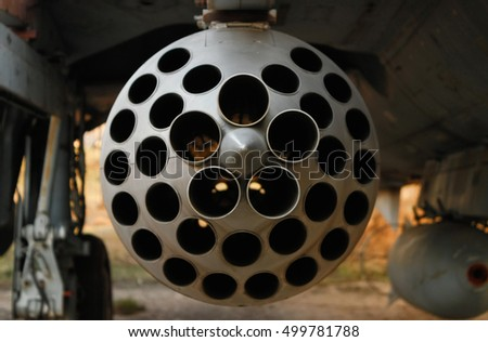 Rocket launcher under the wing of fighter aircraft close-up. Focus on rocket pod