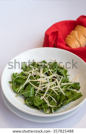 rocket salad with parmesan cheese served with bread in red basket - stock photo