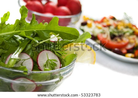 Rocket salad with radish and lemon slice on white background