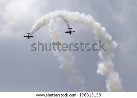 ROCKFORD, IL - JUNE 7: Airplanes from Team Firebirds demonstrates flying skills and aerobatics at the annual Rockford Airfest on June 7, 2014 in Rockford, IL - stock photo