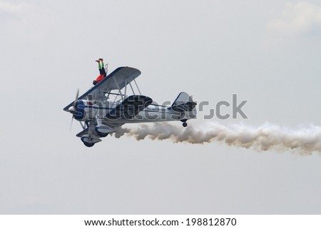 ROCKFORD, IL - JUNE 7: Stunt acrobat Dave Dacy demonstrates balance on a flying airplane at the annual Rockford Airfest on June 7, 2014 in Rockford, IL - stock photo