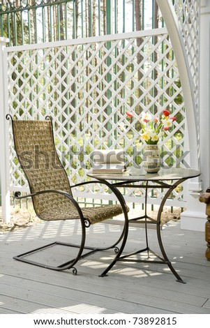 rocking chair and little table on the veranda - stock photo
