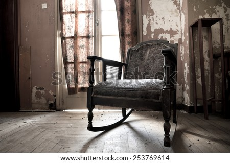 Rocking chair in an old dirty room - stock photo