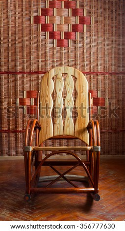 rocking chair made of wood on the wall background wicker, front view
