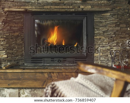 Rocking chair with knit plaid, open book in front of a fireplace, winter cozy concept, soft toned image, selective focus