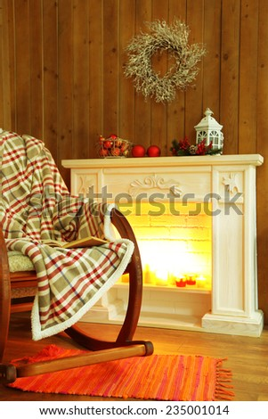 Rocking chair with plaid near fireplace - stock photo