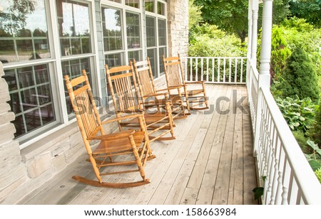 Rocking chairs invite one to relax on an old wooden front porch - stock photo
