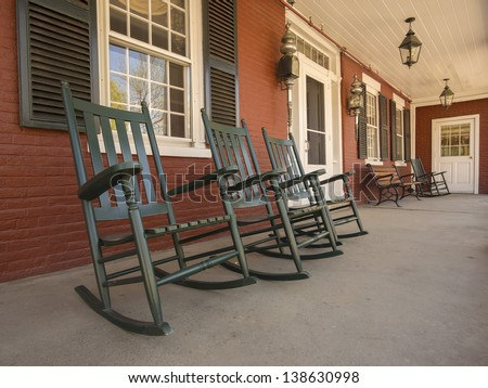 Rocking chairs on porch of historic New England house in Vermont - stock photo
