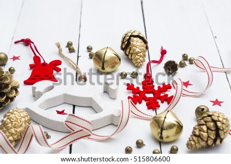 rocking horse, golden cones and red felt Christmas decorations on white wooden table background