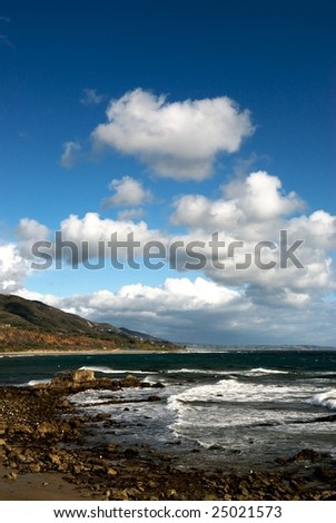 Rocks along Leo Carillo Beach  in southern California with a sky full of white cumulus clouds and waves crashing along the beach