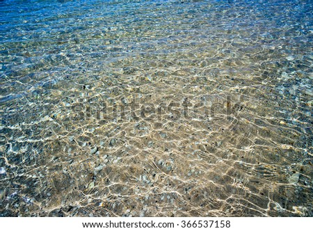Rocks and sand are visible through the clear sea water.