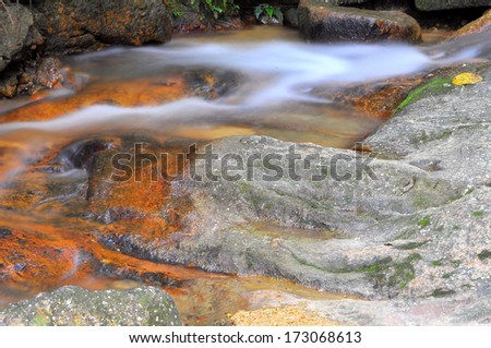 Rocks And Water Flows In A Shallow Stream