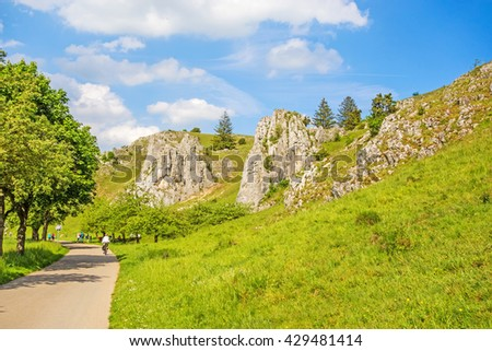 Rocks at valley Eselsburger Tal near river Brenz - jewel of the swabian alps, meadow in front - stock photo