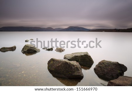 Rocks by the shores of Loch Lomond with Scottish hills in the background at Sunset - stock photo