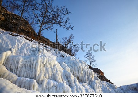 Rocks covered by icicles on winter siberian Baikail lake unber blue sky at evening time - stock photo