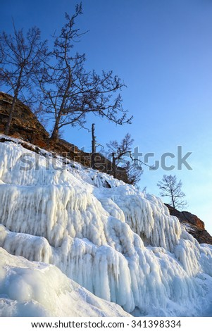 Rocks covered by icicles on winter siberian Baikail lake under blue sky at evening time - stock photo