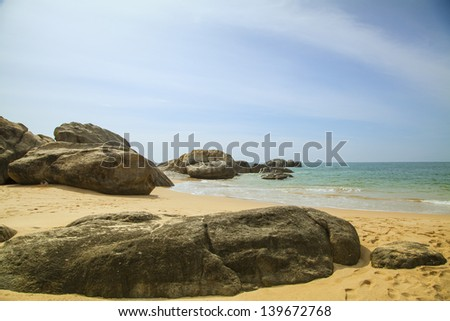 rocks in front of the shining turquoise-blue Indian Ocean at the tropical island Sri Lanka - stock photo