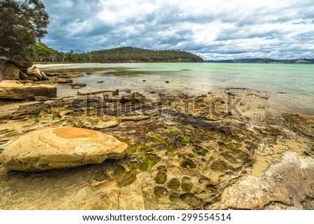 Rocks in Lime Bay beach camping inside the Lime Bay State Reserve, located at the northern end of the Tasman Peninsula to the west of Whitehouse Point. Tasmania, Australia. . - stock photo