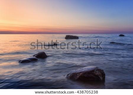 Rocks in the sea at sunset in  Estonia - stock photo