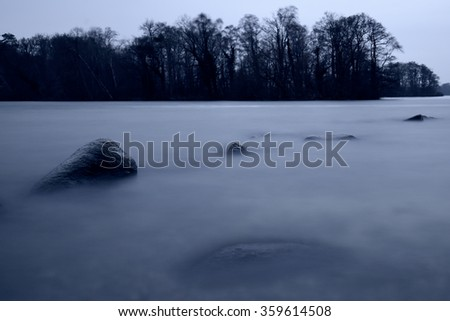 Rocks in the swallow water of a lake - stock photo
