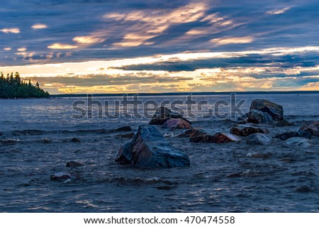 Rocks in water by the sea, while sun is setting