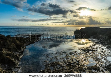 Rocks near the sea. Sunset sky reflected in the pools, scenic sea on the background. Devil's Tear, Nusa Lembongan, Indonesia