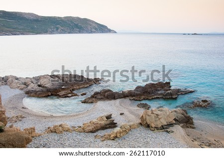 Rocks on sandy beach at sunset of the island of Mykonos. Greece. - stock photo