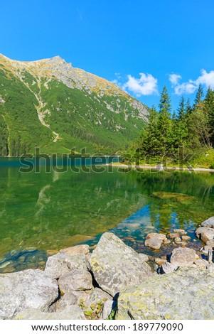 Rocks on shore of green water mountain lake Morskie Oko, Tatra Mountains, Poland - stock photo