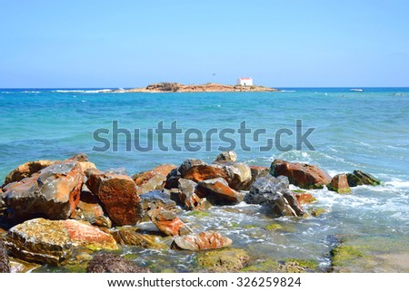 Rocks on the coast of Aegean Sea in Malia, Crete, Greece. In the background the island Afentis Christos.