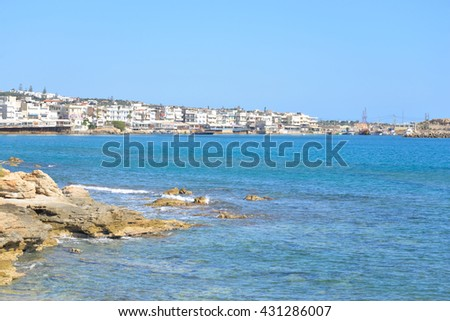 Rocks on the shore of the sea and the city of Hersonissos, Crete, Greece.