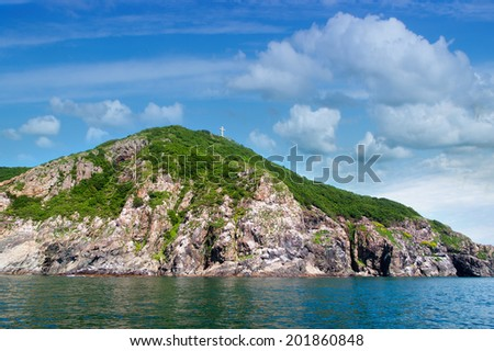 Rocks , sea and Orthodox crosson the  blue sky - Fox Island at the entrance to the port of Nakhodka Russia