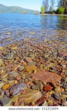 Rocks show through clear waters of a crystal lake.