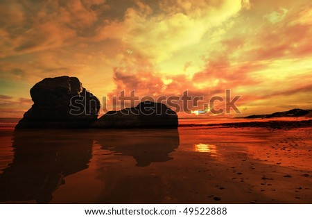 Rocks showing in front of a dramatic sunset