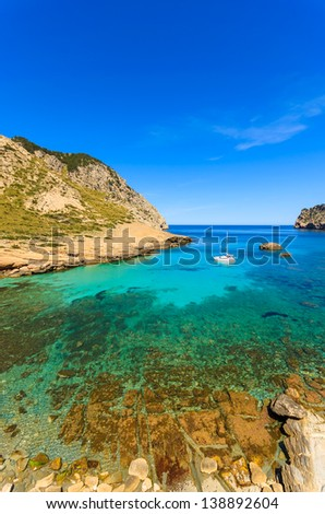 Rocks stones clear water beach bay sea mountains background, Cala Figuera on Cap Formentor, Majorca, Spain