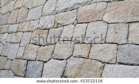 Rocks Wall Background. Wall made of many stones with heterogeneous forms fitted together - stock photo